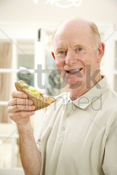 senior man smiling at the camera while holding sandwich stock photo