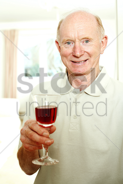 senior man smiling while holding a glass of red wine stock photo