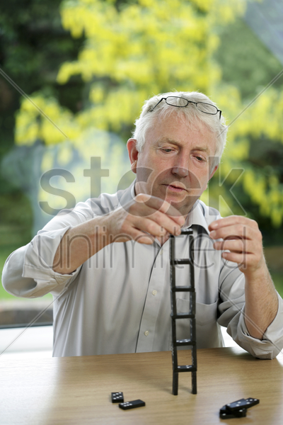 senior man stacking up domino pieces stock photo