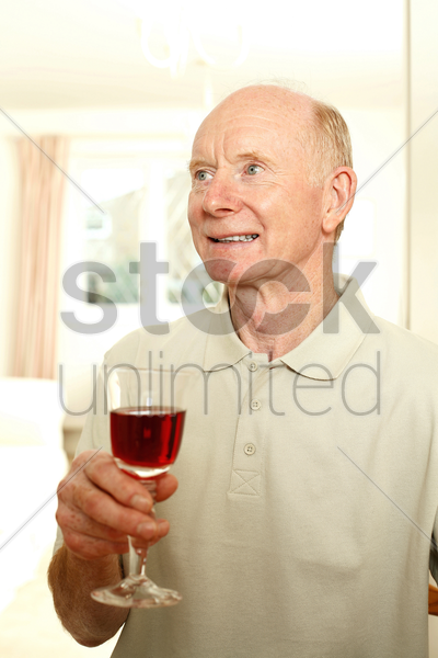 senior man with a glass of red wine stock photo