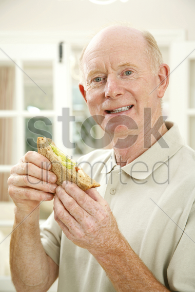 senior man with a sandwich stock photo