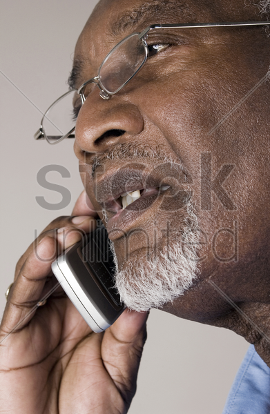 senior man with glasses talking on the phone stock photo