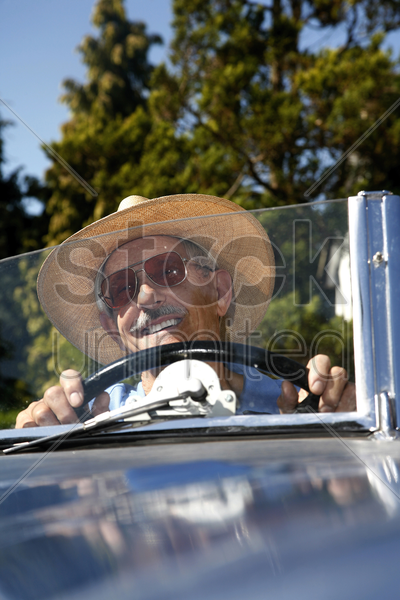 senior man with hat driving in the car stock photo