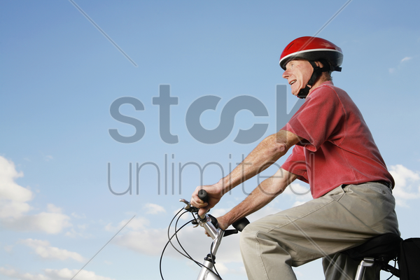 senior man with helmet cycling on bicycle stock photo