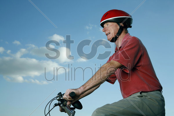 senior man with helmet riding on bicycle stock photo