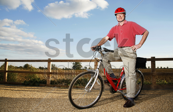 senior man with safety helmet sitting on a bicycle stock photo