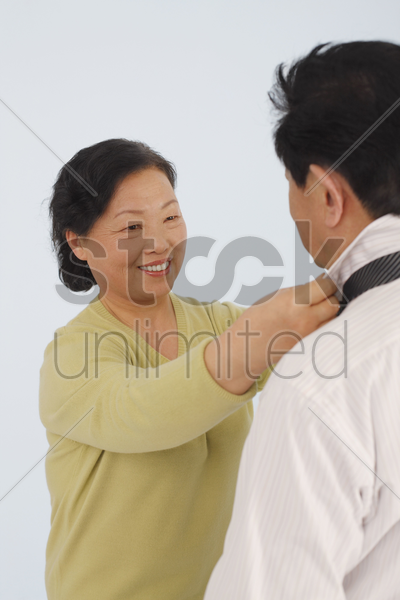 senior woman adjusting senior man's necktie stock photo