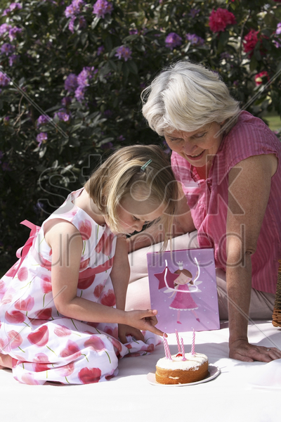 senior woman and girl celebrating birthday in the park stock photo