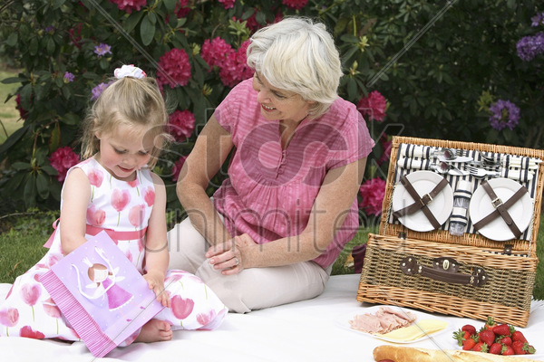 senior woman and girl picnicking in the park stock photo