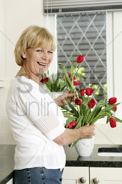 senior woman arranging flowers at home stock photo
