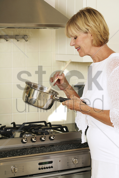 senior woman cooking in the kitchen stock photo