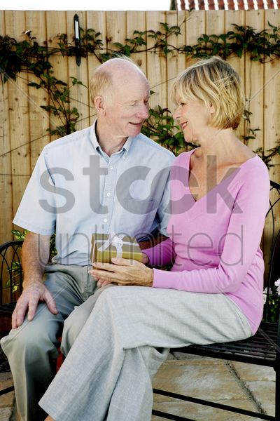 senior woman getting a present from her husband stock photo