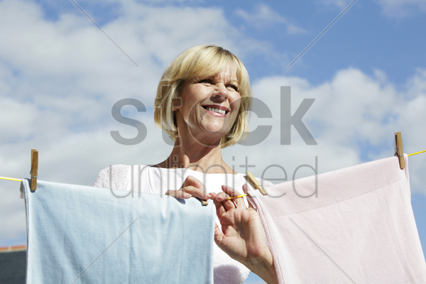 senior woman hanging clothes on the clothesline stock photo