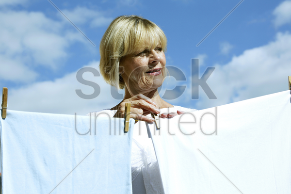 senior woman hanging laundry on washing line stock photo