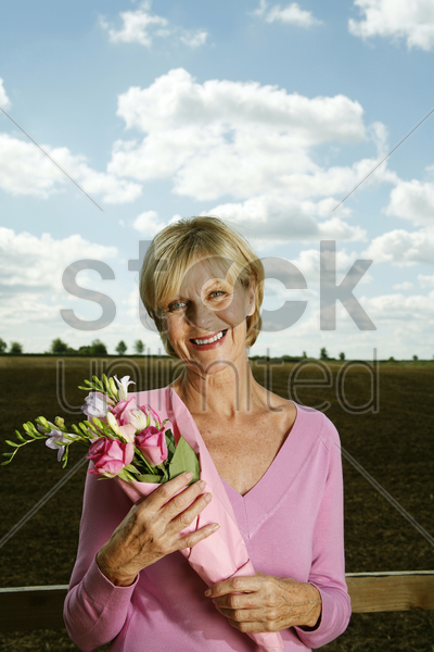 senior woman holding a bouquet of flowers while smiling at the camera stock photo