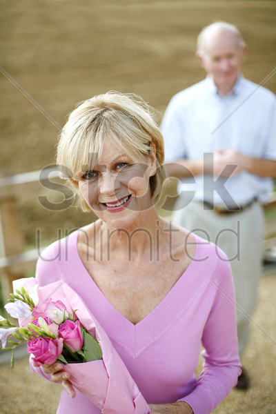 senior woman holding a bouquet of flowers with her husband standing in the background stock photo
