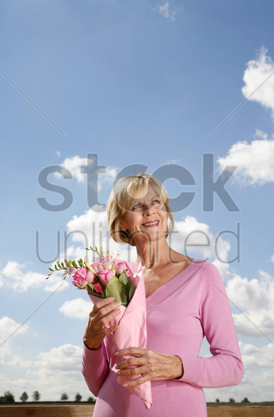 senior woman holding a bouquet of flowers stock photo