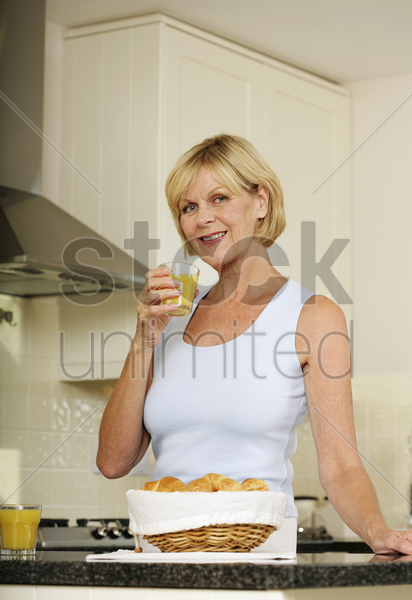 senior woman holding a glass of orange juice while smiling at the camera stock photo
