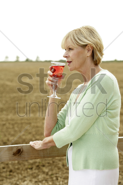 senior woman holding a glass of red wine stock photo