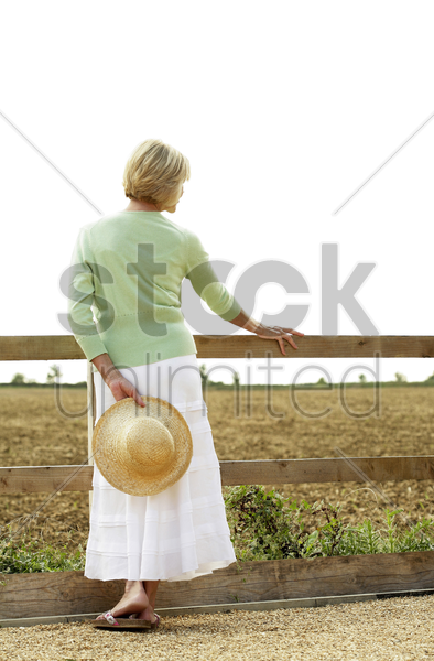 senior woman holding a hat on her back stock photo