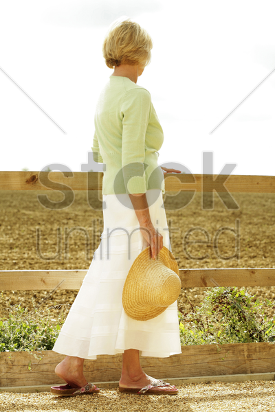 senior woman holding a hat while taking a stroll stock photo