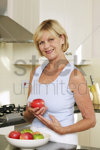senior woman holding a red apple while smiling at the camera stock photo