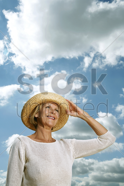 senior woman holding her hat while looking up stock photo