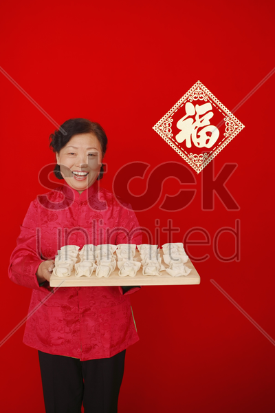 senior woman holding up cutting board with chinese dumplings stock photo