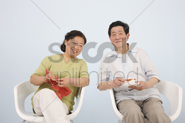 senior woman knitting while senior man is enjoying a cup of tea stock photo