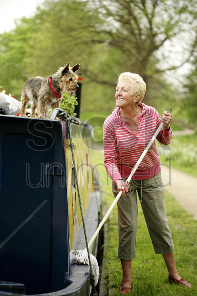 senior woman looking at her dog while mopping her houseboat stock photo