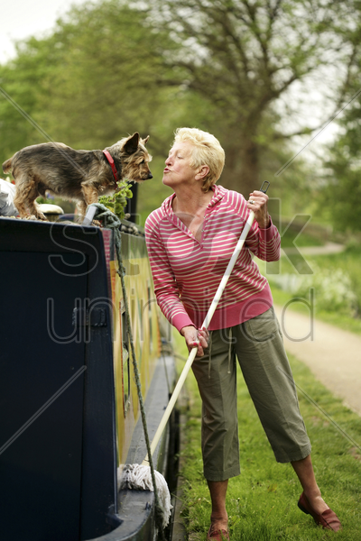 senior woman playing with her dog while mopping her houseboat stock photo