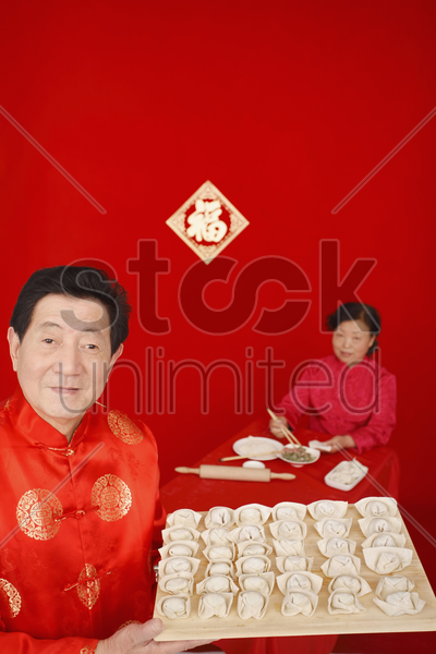 senior woman preparing chinese dumplings, senior man holding up cutting board of chinese dumplings stock photo