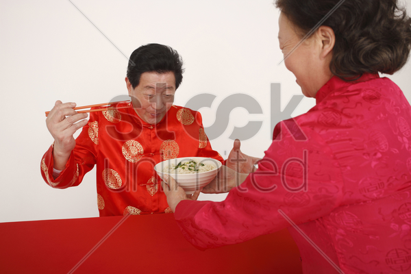 senior woman serving a bowl of noodles to senior man stock photo