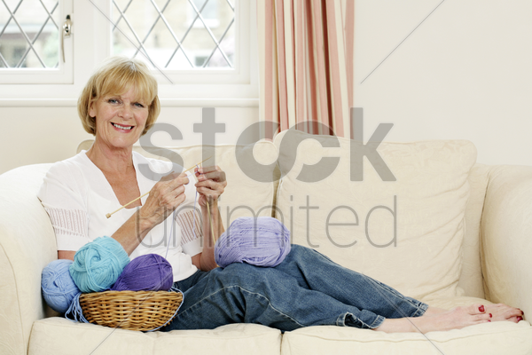 senior woman sitting on the couch knitting stock photo