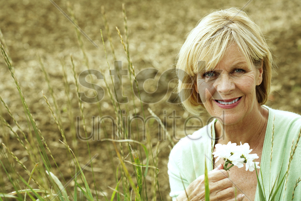 senior woman smiling at the camera while holding white flowers stock photo