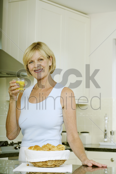 senior woman smiling while holding a glass of orange juice stock photo