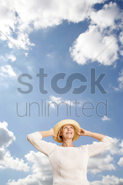 senior woman smiling while holding her hat stock photo