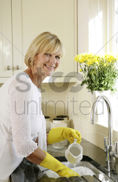 senior woman washing dishes in the sink stock photo