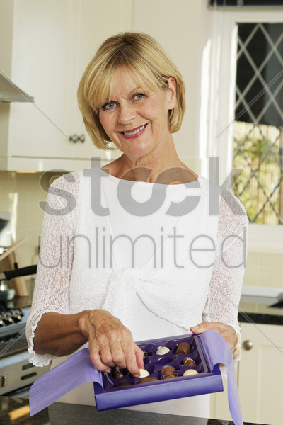 senior woman with a box of chocolates smiling at the camera stock photo