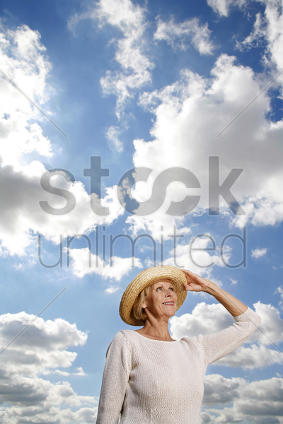 senior woman with hat smiling while looking up stock photo