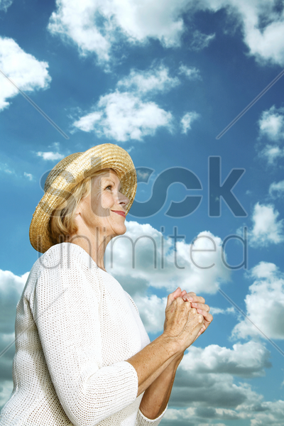 senior woman with her hands clasped together stock photo