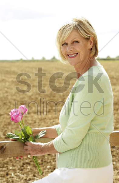 senior woman with pink roses smiling at the camera stock photo