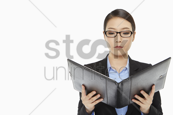 serious businesswoman reading notes from a folder stock photo