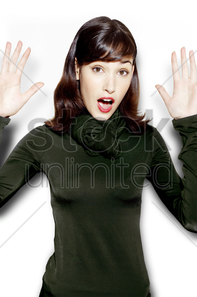 shocked woman raising her hands stock photo