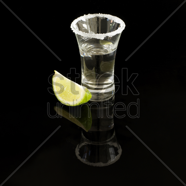 shot of tequila with salt rimmed glass and wedge of lime stock photo