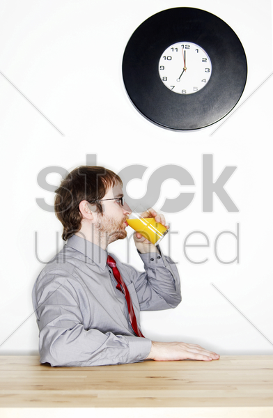 side shot of a bespectacled man drinking a glass of orange juice for his breakfast stock photo