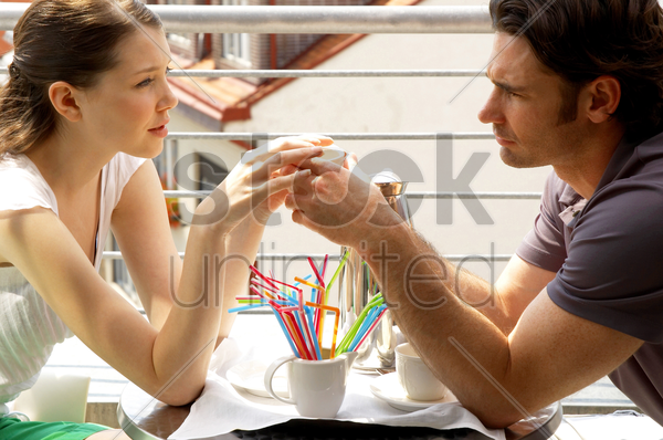 side shot of a couple holding a cup together stock photo