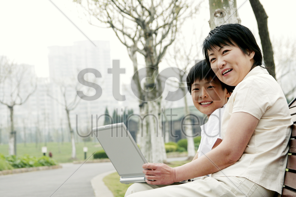 side shot of a woman and her son sitting on the bench with a laptop on their laps stock photo