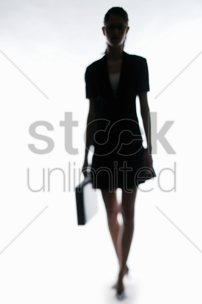 silhouette of businesswoman carrying a briefcase stock photo