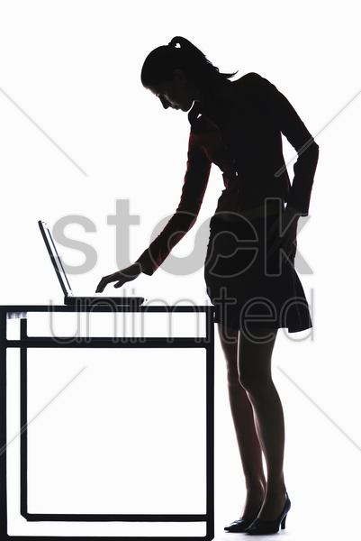 silhouette of businesswoman using laptop stock photo